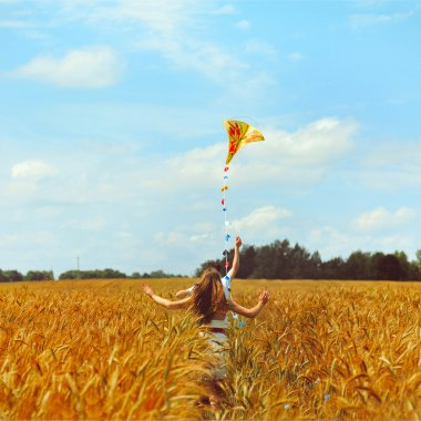 Young couple in love running with a kite in a yellow box