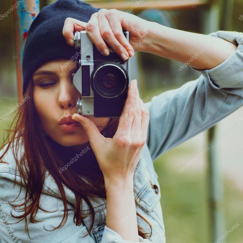 5ebf486cc0380 Retrato de una muchacha hermosa hipster en una gorra y una chaqueta de  mezclilla con una cámara tomando fotos - fotos  muchachas con gorras — Foto  de ...
