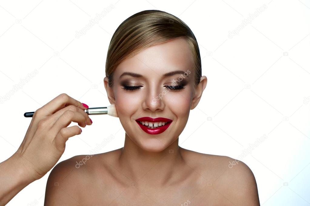 Makeup Artist applying Powder Foundation with Brush. Beauty and health clean Skin of young smiling Woman with smoky Eyes and red Lips.