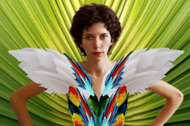 Young beautiful girl in the image of a parrot in a brightly colored feathers and wings