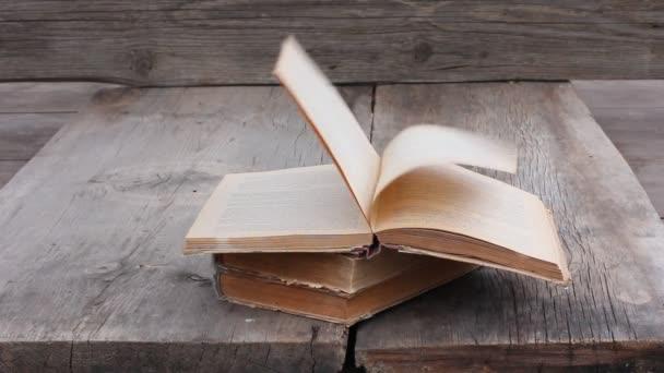 kupu starých knih o šedé prken. silný nárazový vítr otočí stránky otevřené knihy. Kopírovat prostor