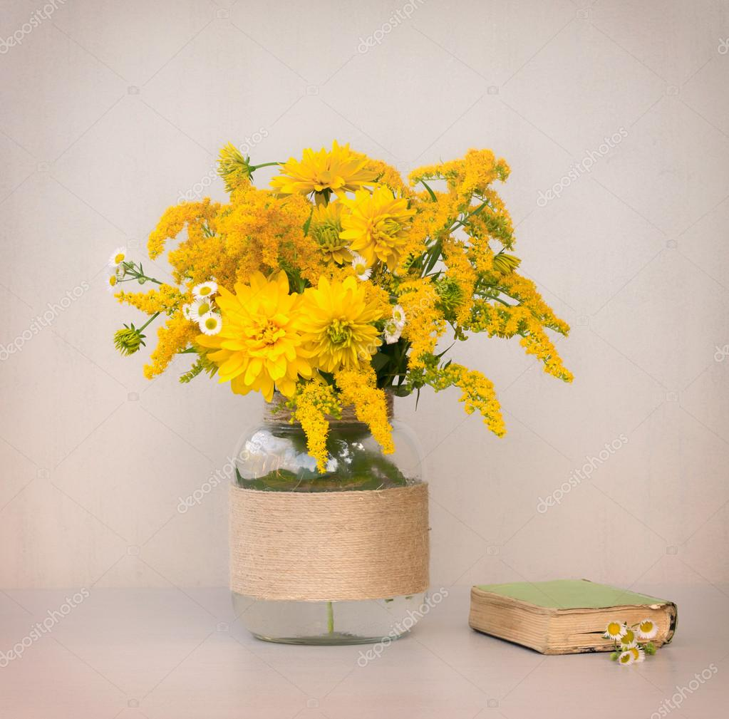 Little old book a bouquet of flowers chrysanthemums goldenrod little old book a bouquet of flowers chrysanthemums goldenrod and daisies in a glass vase homemade closeup on gray background closeup tinted photo reviewsmspy