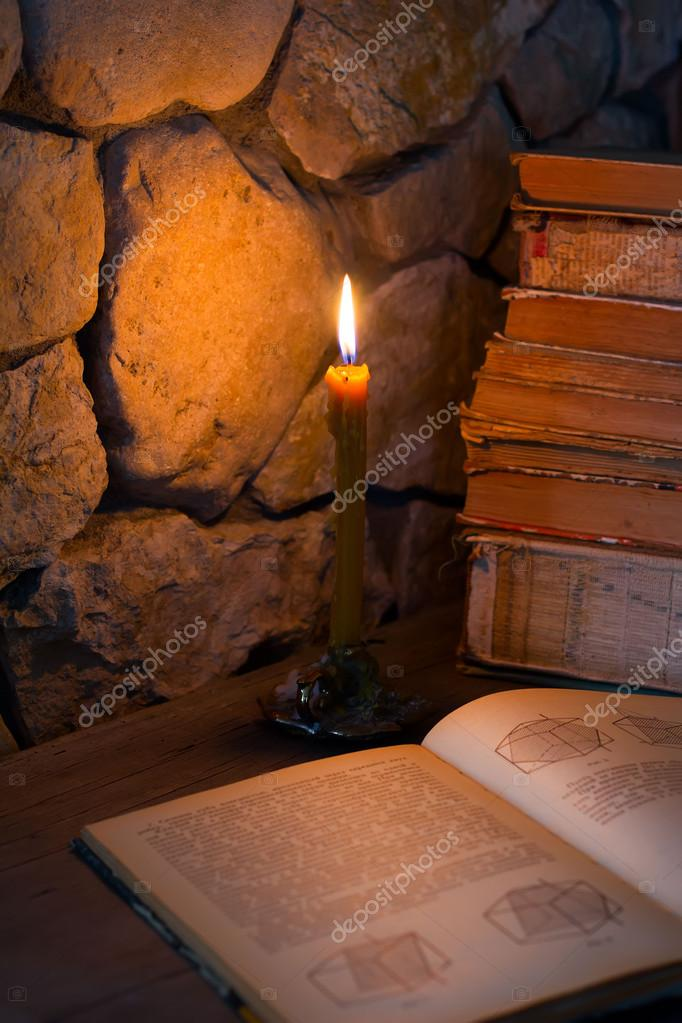 burning candle and old books
