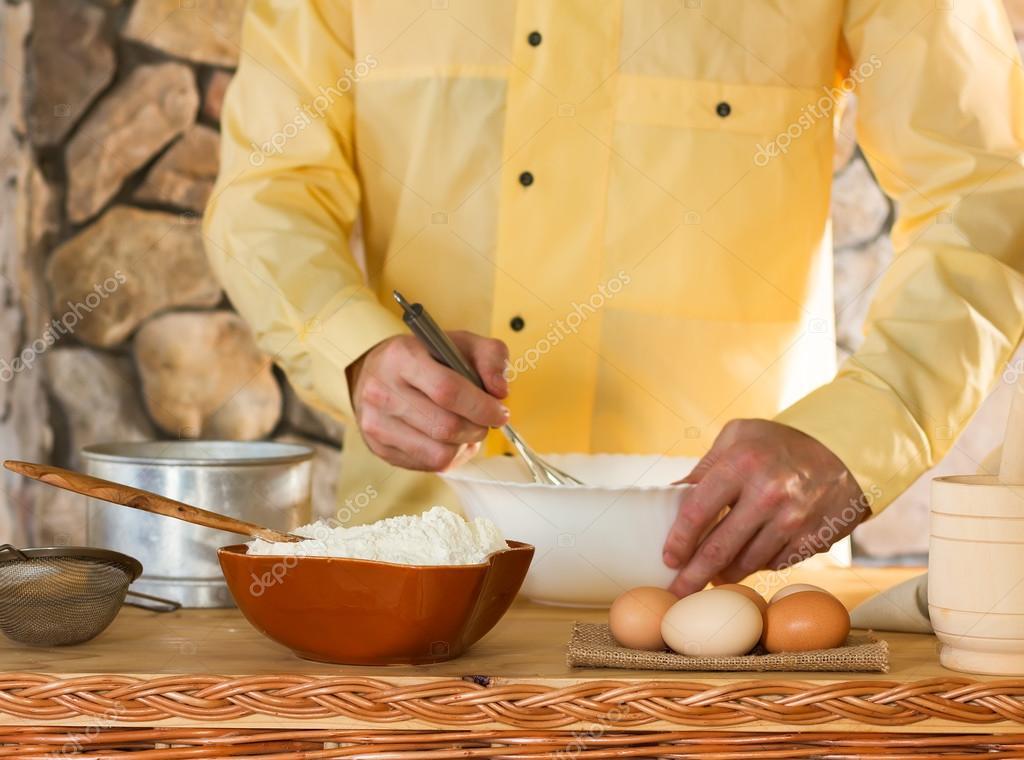 im Vordergrund steht eine Schüssel mit Mehl, Eier, ein Sieb und ...