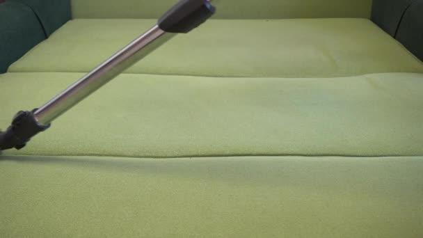 Muž profesionální uklízeč, odstraňuje vlnu z pohovky. Velký moderní prací vysavač