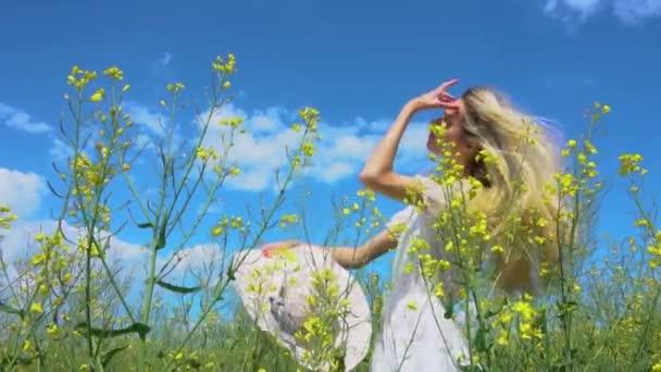 Junges schönes Mädchen richtet sich auf und setzt im Sommer einen breiten Hut in einem blühenden Rapsfeld auf