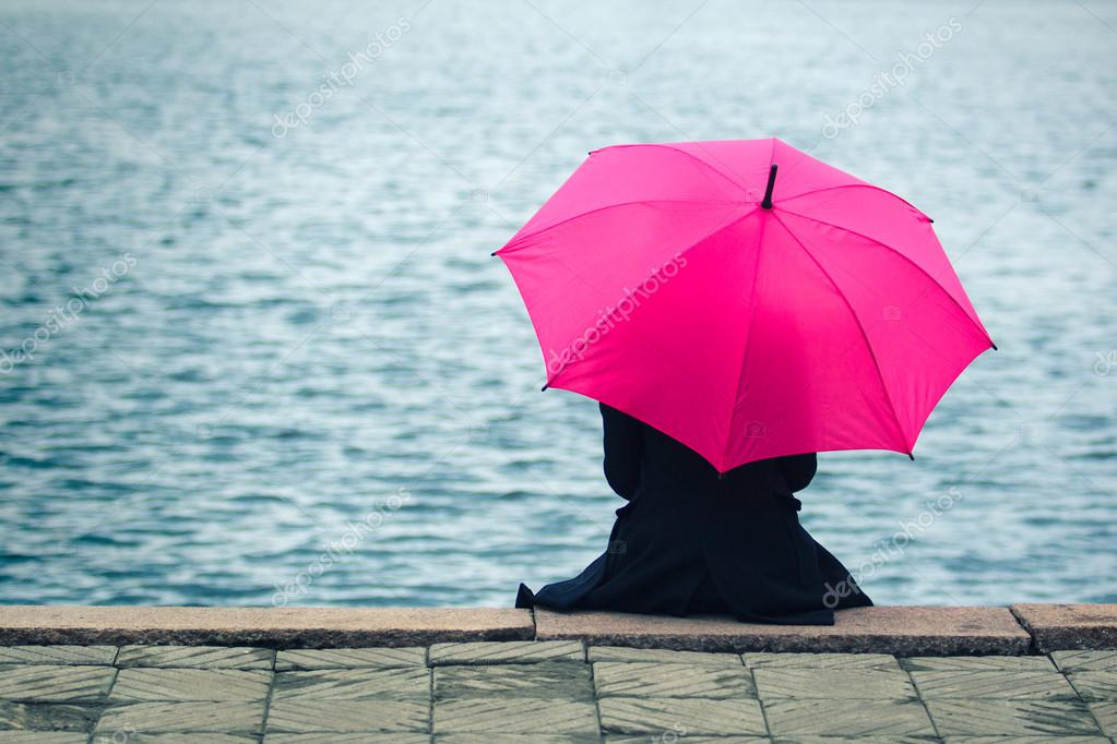Woman sitting lonely with pink umbrella.