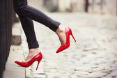 Fotografie Frau trägt schwarze Lederhosen und rote high Heels Schuhe in Altstadt