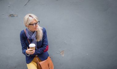 Trendy young woman standing at the wall outdoors and holding a cup of coffee.