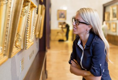 Caucasian woman contemplating colorful paintings displayed in front of her