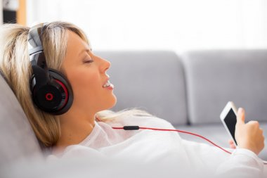 Relaxed woman listening to music on headphones at home stock vector