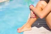 Fotografie Žena sedí na terase u bazénu