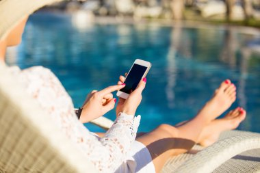 Woman sitting in deck chair and using mobile phone