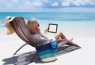 Woman relaxing on the beach and listening to music on her digital tablet computer
