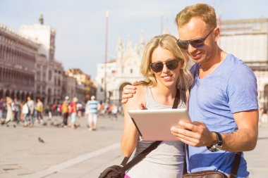 Couple looking at tablet computer while traveling in Venice