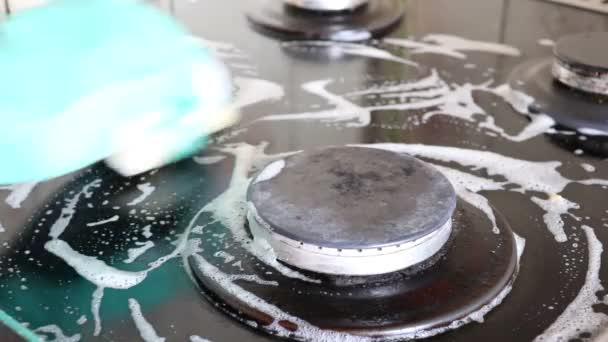 Úklid kuchyně. Žena v zelené ochranné gumové rukavice čištění kuchyňského nábytku