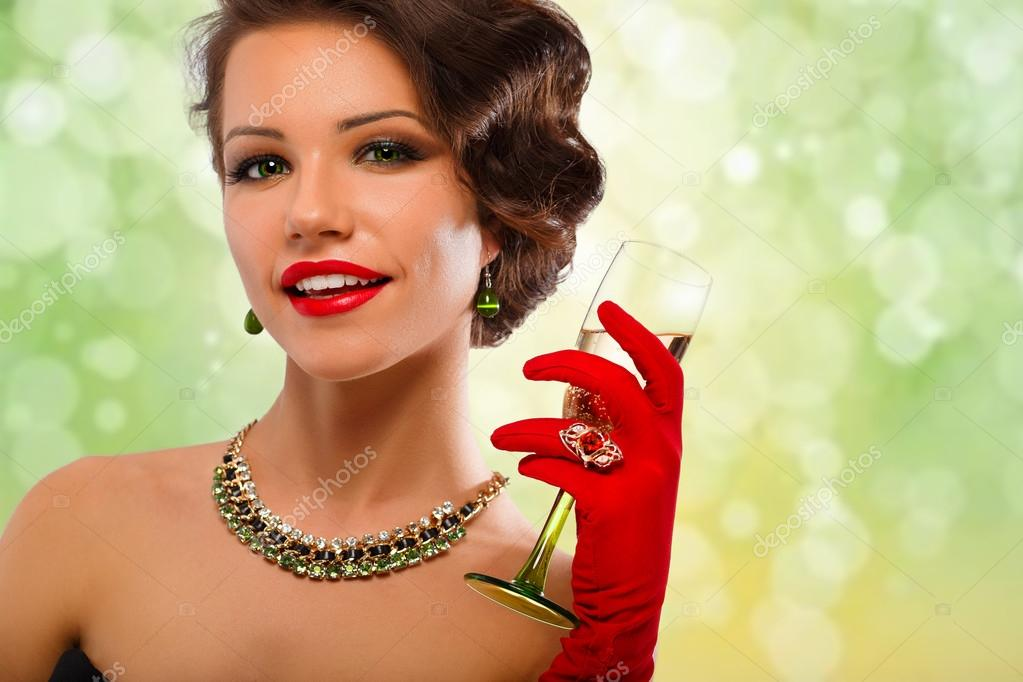 Sexy model woman with glass of champagne in red gloves and chic jewelry