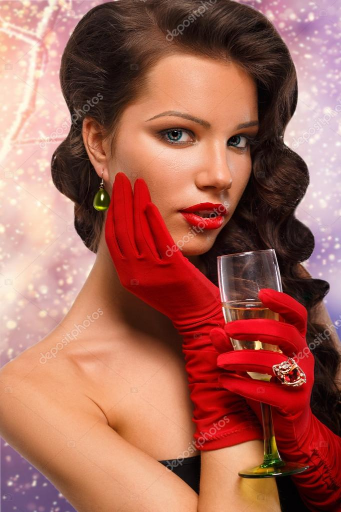 Isolated Glamour girl in red gloves holding a glass of champagne.