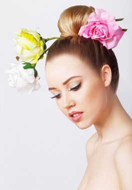 Fashion Beauty Model Girl with Rose Flowers Hair. Make up and Hair Style. Hairstyle.Bouquet of Beautiful Flowers on lady's head