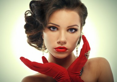 Glamour girl in red gloves holding hands near face. Vintage Style Mysterious Woman Wearing Red Gloves.