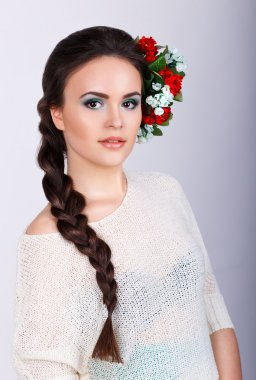 Girl with long dark plait and flowers in her hair.Studio portrait of a beautiful brunette girl