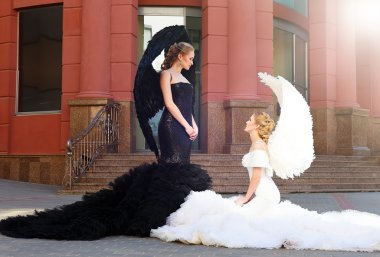 two angels.  black angel standing over white angel