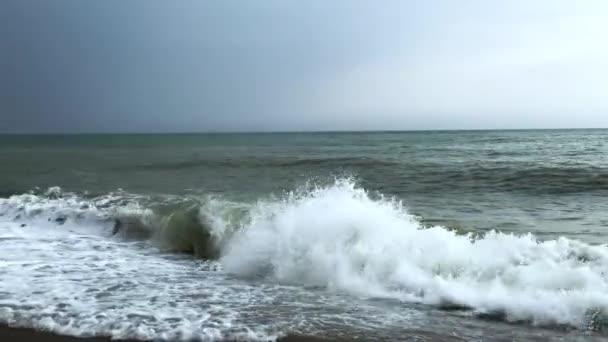 Pěnové vlny drsného moře dopadly na břeh v zamračený den.