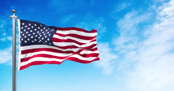 The national flag of the United States of America waving in the wind. Clear sky in the background. Selective focus. Democracy, independence and election day. Patriotic symbol of American pride