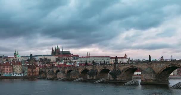 Včas barevné dramatické oblohy a řeky Vltavy při západu slunce nad Karlovým mostem a Pražským hradem ve starém městě Praze, hlavním městě České republiky.