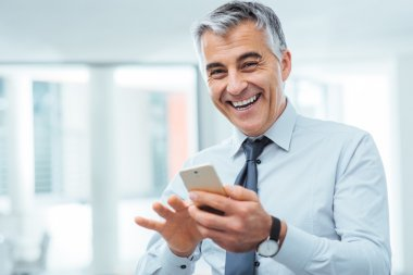 Smiling businessman using a smart phone