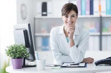 Attractive young female doctor leaning on the clinic reception desk with hand on chin, she is smiling at camera, medical staff and healthcare concept stock vector