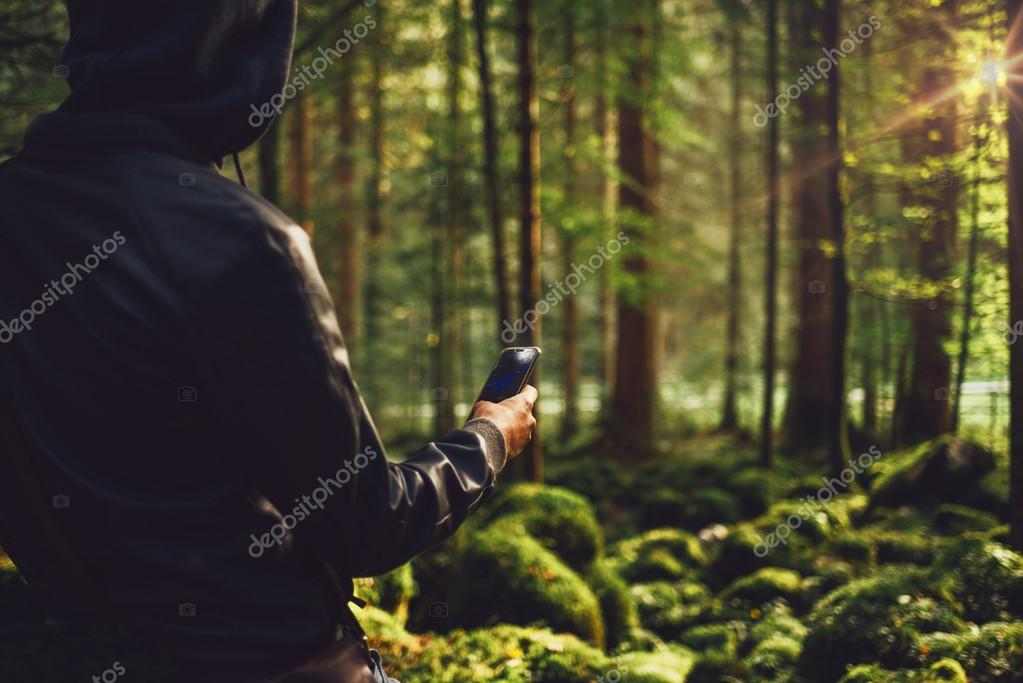 Man taking pictures in the woods