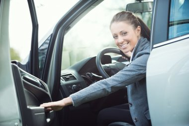 Young woman opening car door