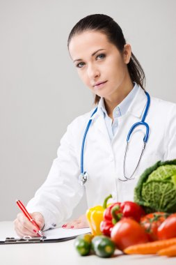 Smiling nutritionist writing medical prescriptions