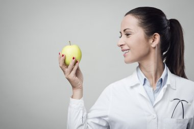 Smiling nutritionist with apple
