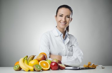 Confident nutritionist working at desk with fresh fruit stock vector