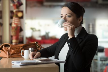 Attractive woman having a coffee break at the bar, she is drinking a cup of coffee and staring at the window stock vector