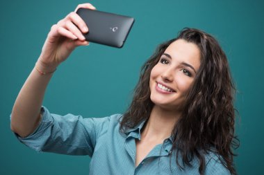 Cheerful girl taking a selfie with her mobile touch screen smartphone stock vector