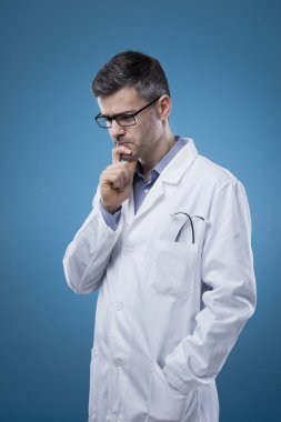 Pensive doctor with lab coat thinking with hand on chin stock vector