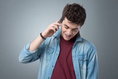 Smiling teenager having a phone call