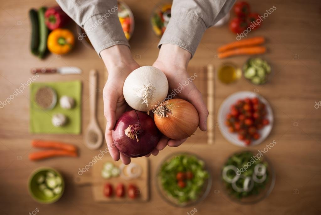 Hands holding different types of onions