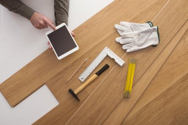 Carpenter installing a wooden floring and using a tablet