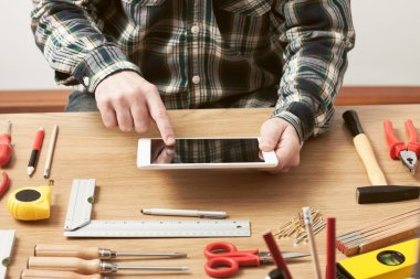 Craftsman working on a DIY project with his tablet