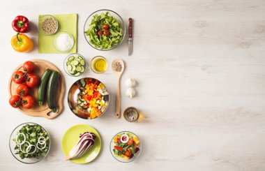 Healthy eating concept with fresh vegetables and salad bowls on kitchen wooden worktop, copy space at right, top view stock vector