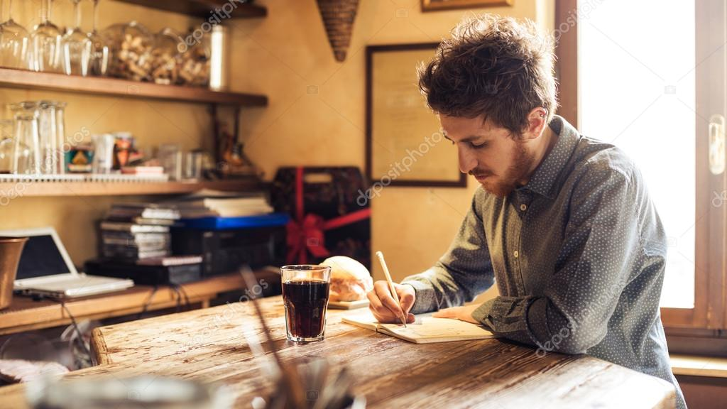 Young hipster man sketching in his studio