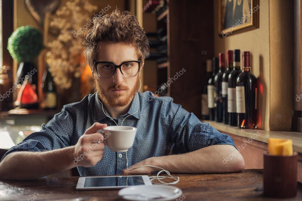 Nerd guy with tablet at the bar