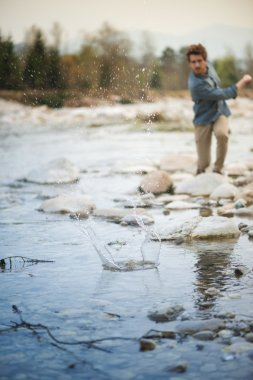 Man throwing stones in the river