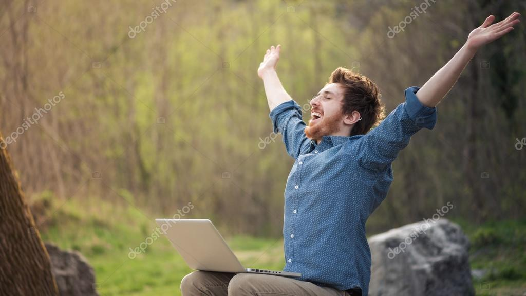 Happy hipster with laptop in the forest