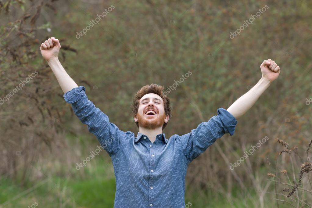 Cheerful hipster with raised fists