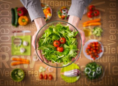 Hands holding an healthy fresh vegetarian salad in a bowl, fresh raw vegetables on background and healthy eating text concepts stock vector